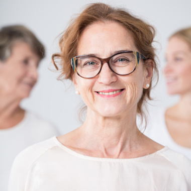 Portrait of smiling mature woman in glasses with family